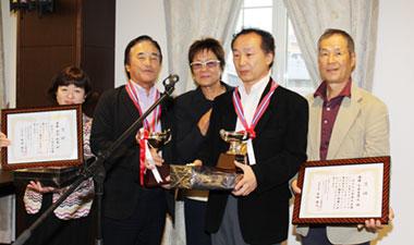 優勝した石内利光さんとガイドの齋藤芳子さん(左側・レギュラー)、千木良孝之さんとガイドの武藤規雄さん(右側・チャレンジ)、中央は岡田美智子プロ2